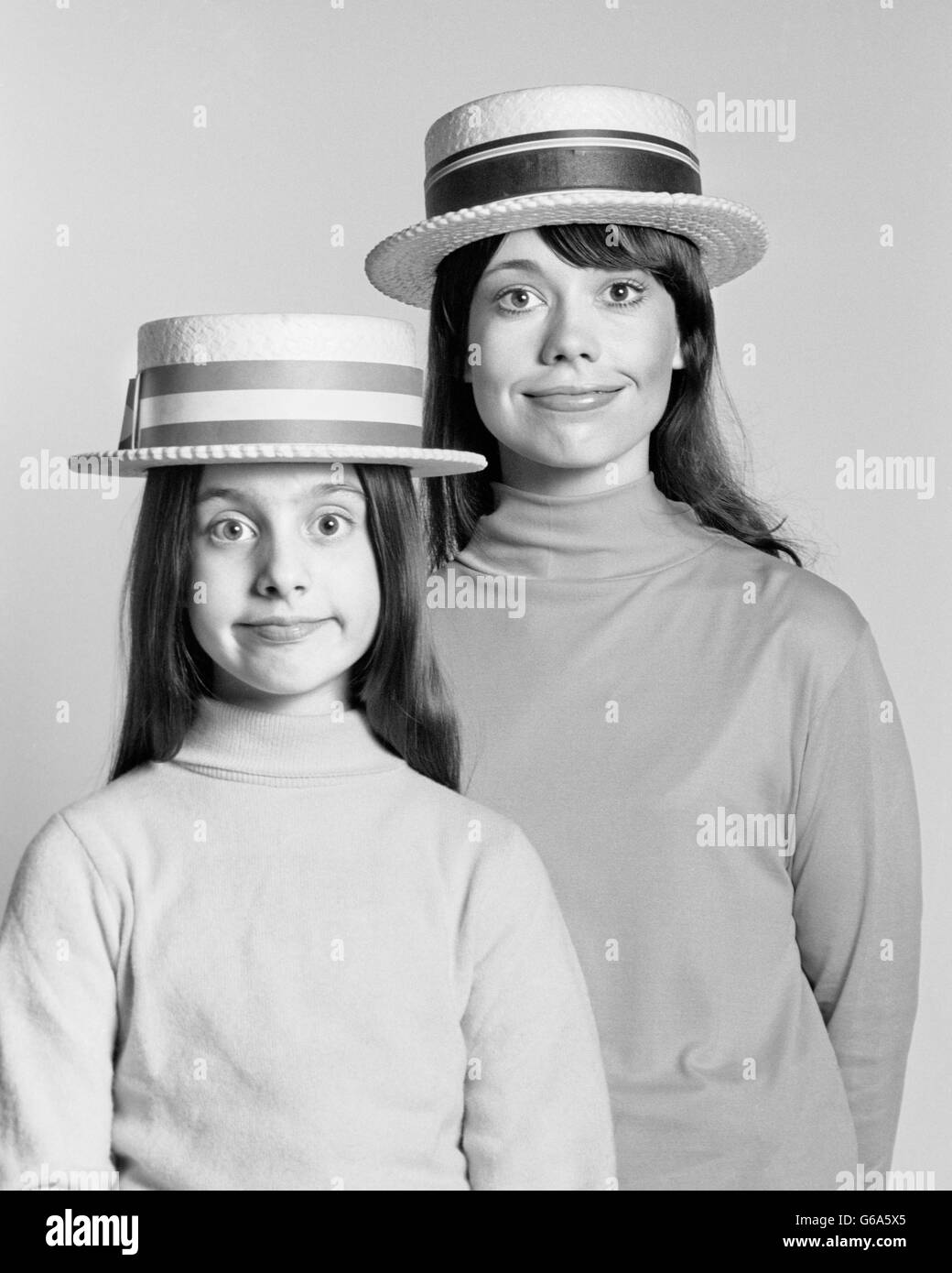 1970s MOTHER AND DAUGHTER PORTRAIT LOOK ALIKE SILLY FACIAL EXPRESSION STRAW BOATER HATS - Stock Image