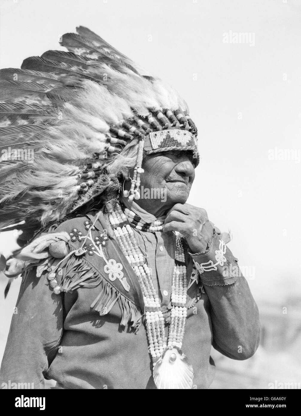 1930s NATIVE AMERICAN MAN CHIEF WEARING FULL FEATHERED HEADDRESS BEADED COSTUME SANTA CLARA PUEBLO NEW MEXICO USA - Stock Image