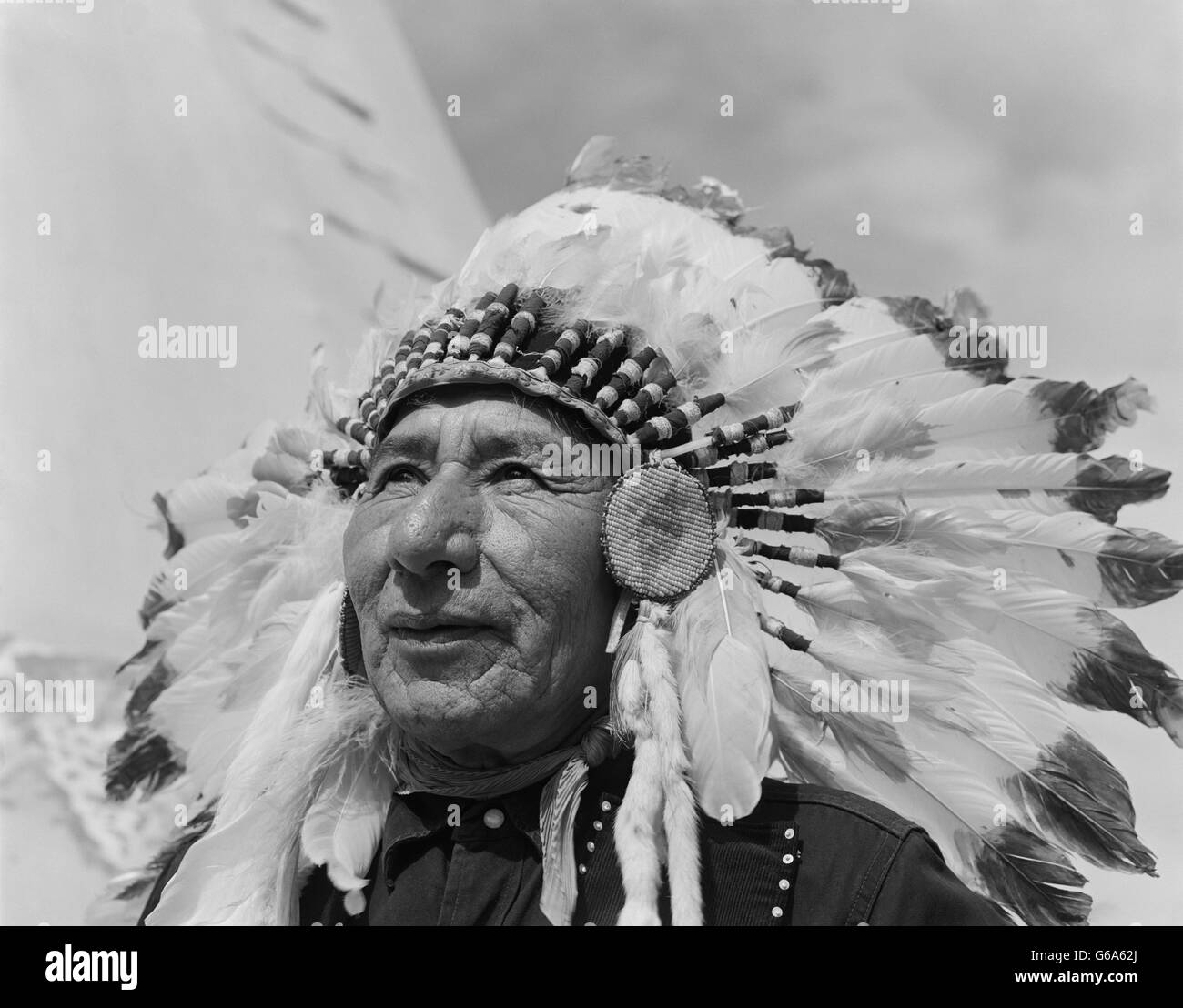 1960s PORTRAIT CHIEF GULL STONEY SIOUX NATIVE AMERICAN MAN WEARING FEATHERED HEADDRESS MORLEY RESERVATION ALBERTA - Stock Image