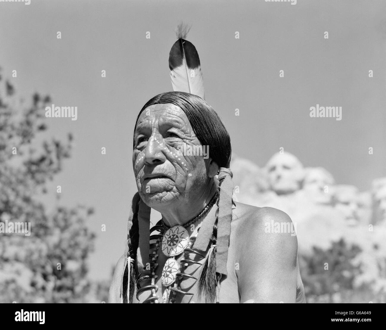 1950s 1960s NATIVE AMERICAN SIOUX INDIAN MAN WITH MOUNT RUSHMORE SOUTH DAKOTA IN BACKGROUND - Stock Image