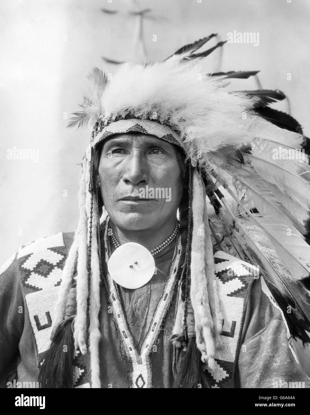1920s PORTRAIT NATIVE AMERICAN INDIAN MAN CHIEF SITTING EAGLE IN FULL HEADDRESS STONEY TRIBE OF BANFF ALBERTA CANADA - Stock Image