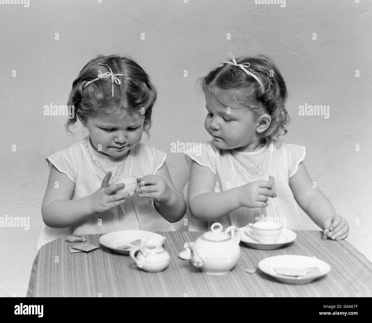 1930s 1940s TWIN GIRLS HAVING TEA PARTY TOY DISHES CUPS TABLE - Stock Image