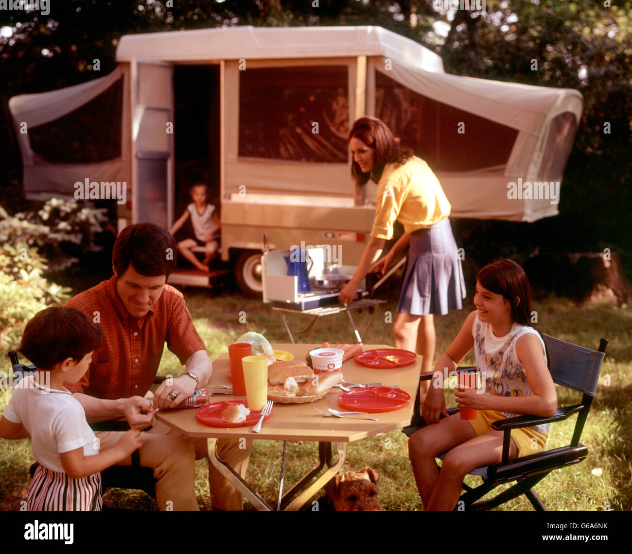 1970s FAMILY CAMPING VACATION CAMPSITE MOTHER COOKING ON CAMP STOVE FATHER AND KIDS AT TABLE EATING