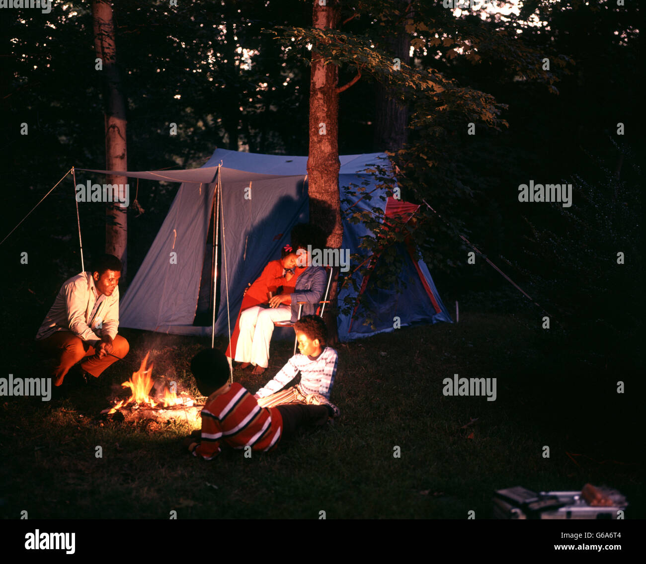 1970s AFRICAN AMERICAN FAMILY CAMPING WITH TENT NIGHT SHOT SITTING AROUND CAMPFIRE