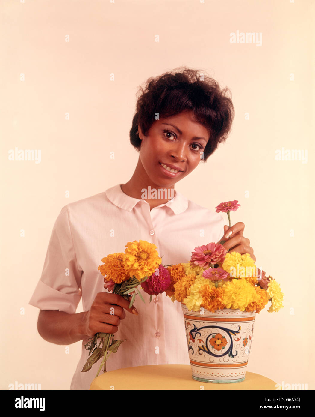 1970s PORTRAIT SMILING AFRICAN AMERICAN WOMAN ARRANGING FLOWERS - Stock Image