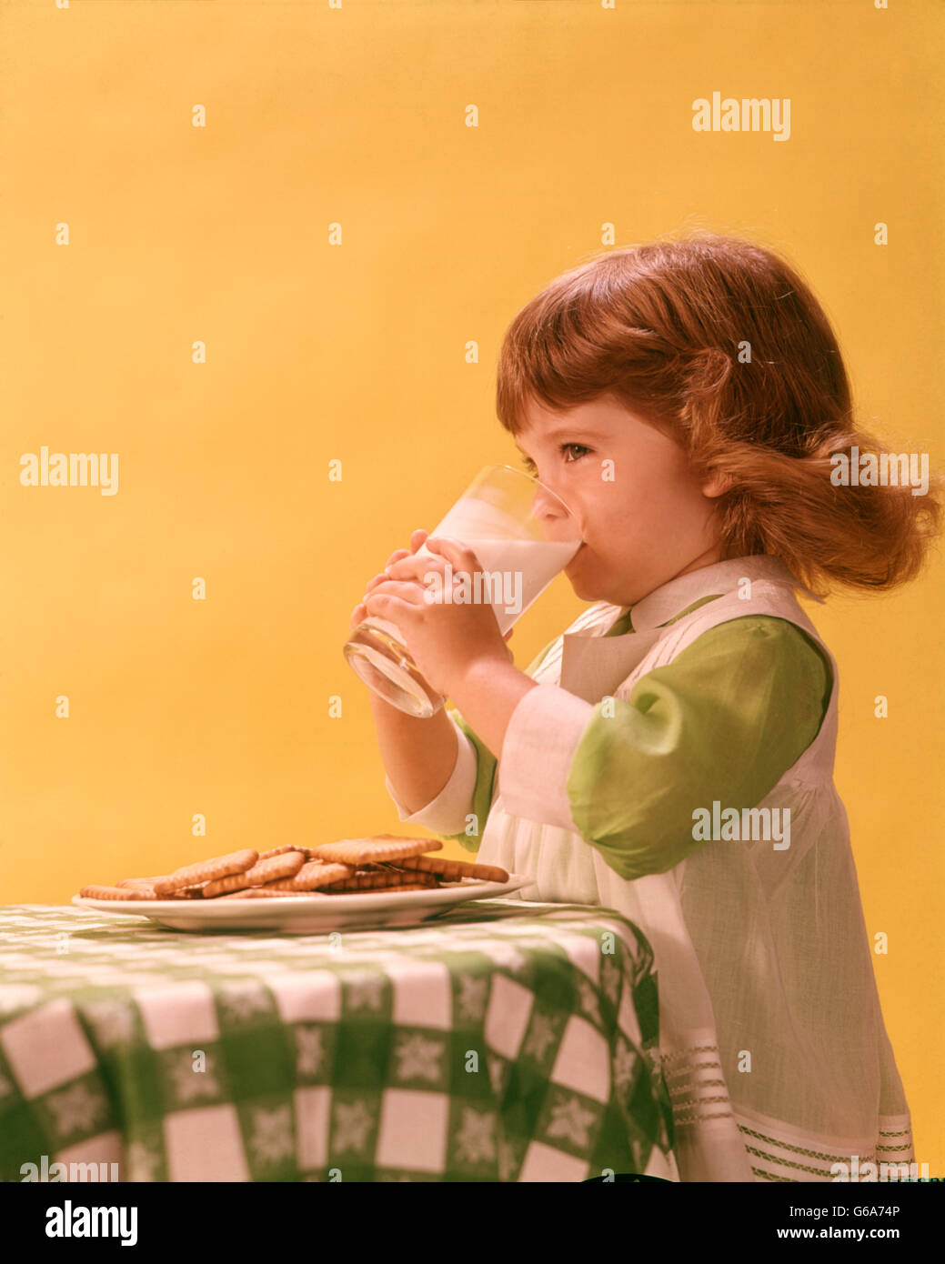 1970s 1960s GIRL DRINKING  GLASS OF MILK COOKIES ON TABLE - Stock Image