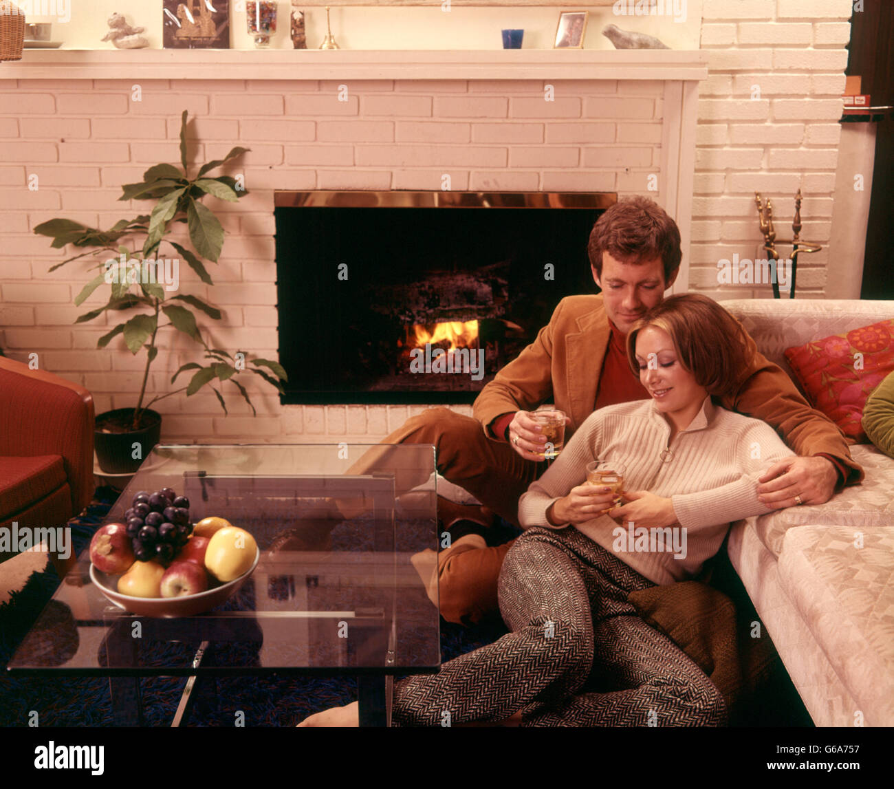1970s ROMANTIC COUPLE MAN AND WOMAN HAVING DRINKS BY FIREPLACE SITTING ON FLOOR - Stock Image