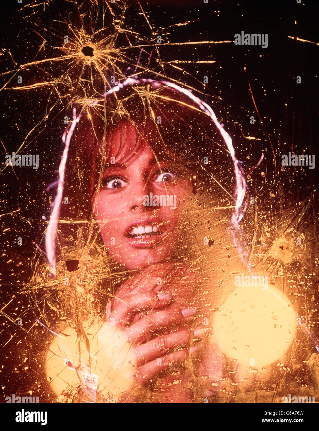 1970s WOMAN AFRAID LOOKING AT CAMERA FACIAL EXPRESSIONS FEAR TERROR FRIGHT YELLOW CAR HEADLIGHTS SHATTERED GLASS - Stock Image