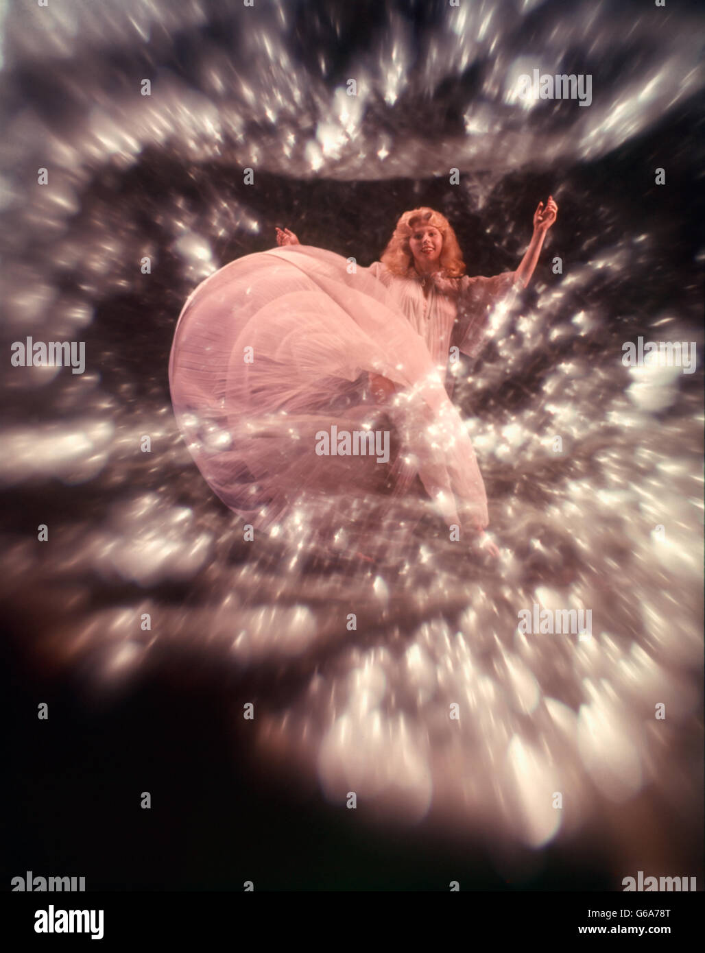 1960s BLONDE WOMAN SHEER PINK WHITE GOWN DANCING TURNING SWIRLING BLUR STAR BACKGROUND BUBBLES MUSIC DANCE - Stock Image