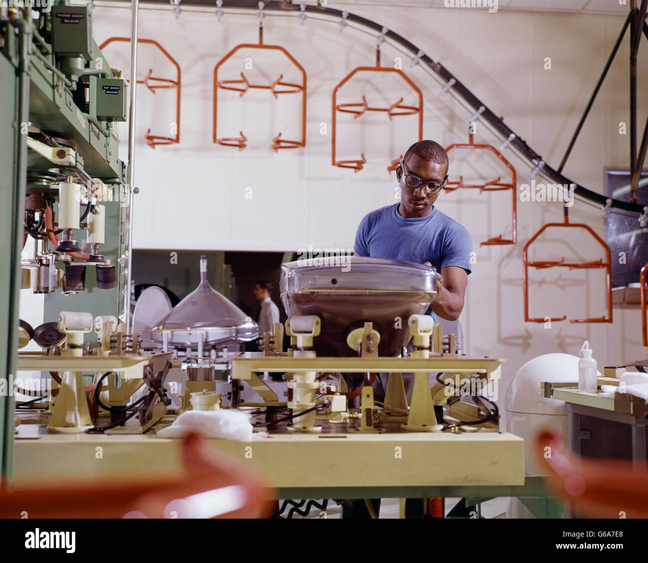 1960s AFRICAN AMERICAN MAN IN FACTORY ASSEMBLY LINE LAMINATING FACE OF COLOR TV PICTURE TUBE - Stock Image