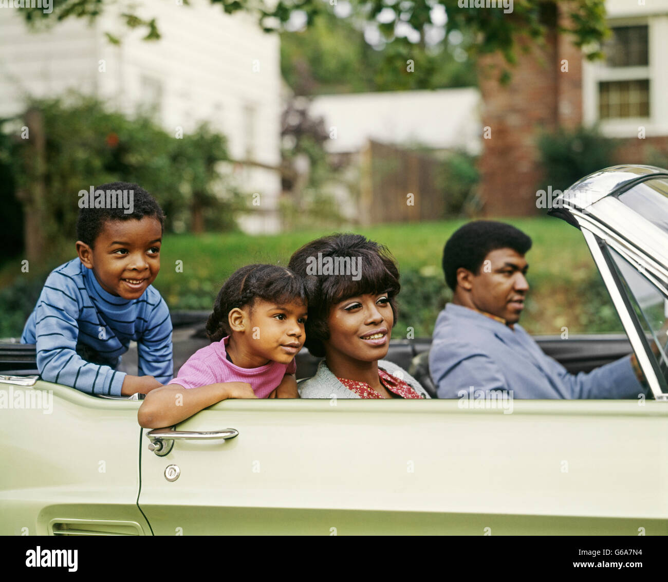 1970s AFRICAN AMERICAN FAMILY OF FOUR RIDING IN CONVERTIBLE AUTOMOBILE FATHER MOTHER SON DAUGHTER - Stock Image