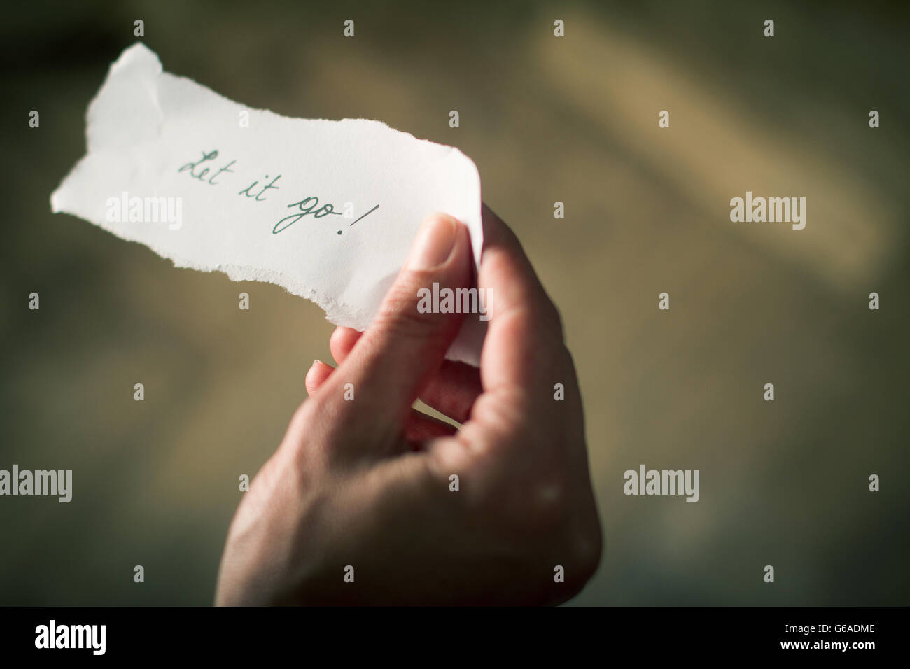 Hand holding a note of paper with the message let it go written on it - Stock Image
