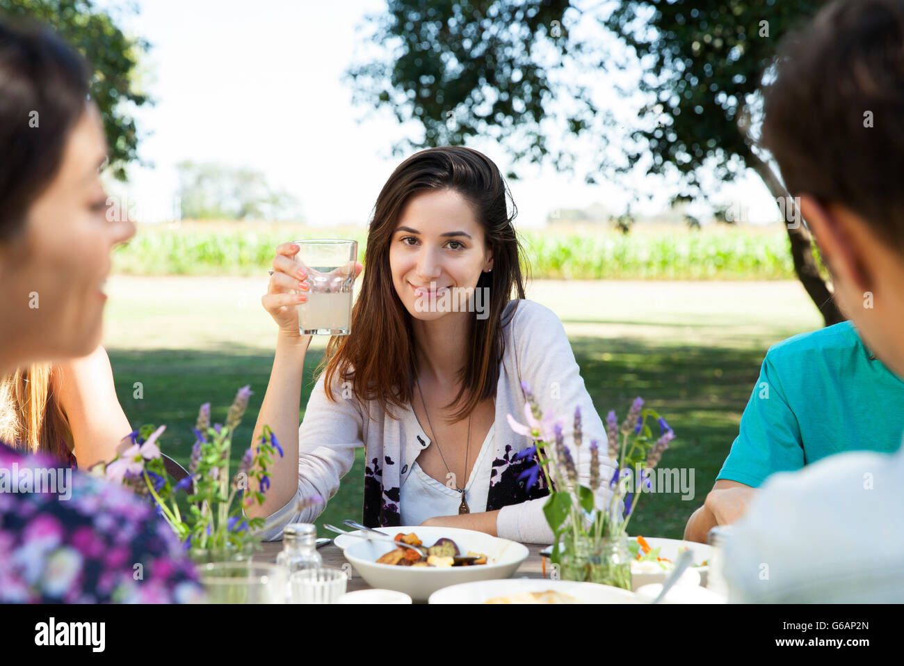 Woman enjoying meal with friends Stock Photo