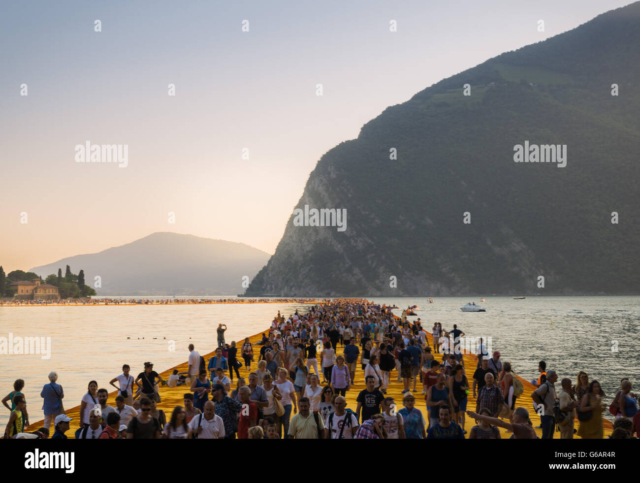 The Floating Piers Christo project. Visitors walking from Sulzano to Monte Isola and to the island of San Paolo. - Stock Image
