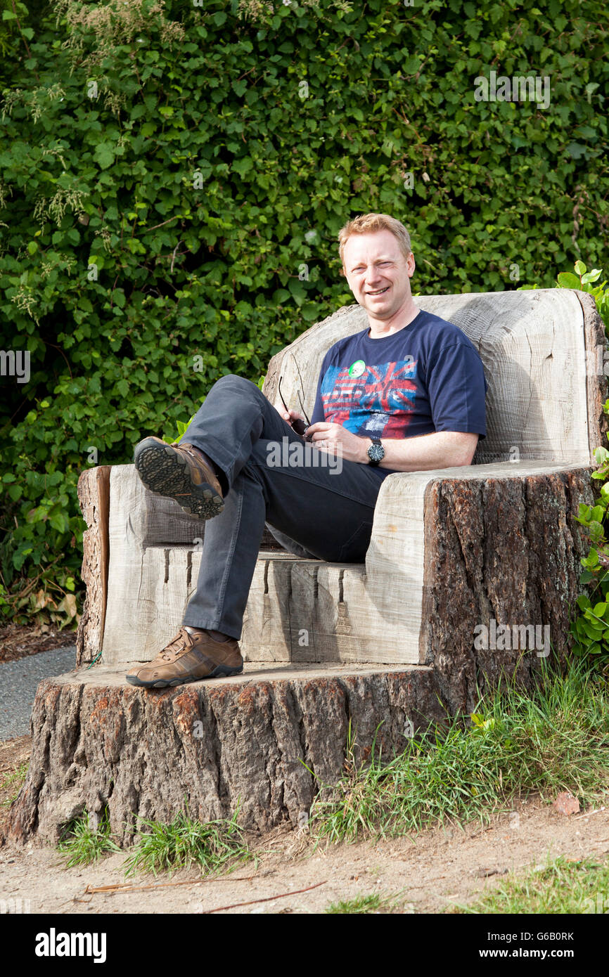 A man sits on a seat carved from a tree stump - Stock Image