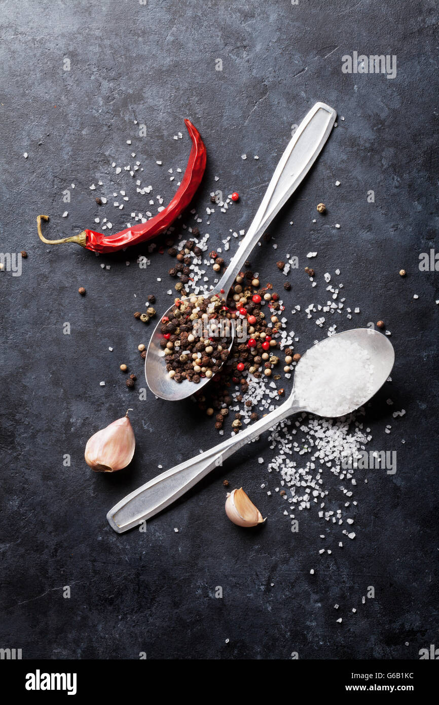 Garlic, black, white and red pepper and salt spices in spoon. Top view - Stock Image
