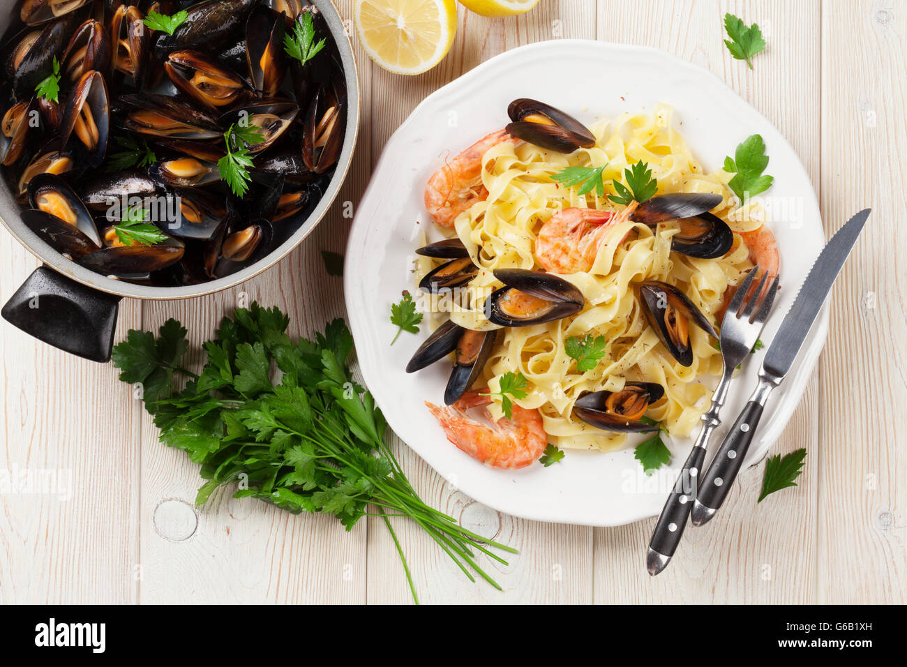 Pasta with seafood on wooden table. Mussels and prawns. Top view - Stock Image