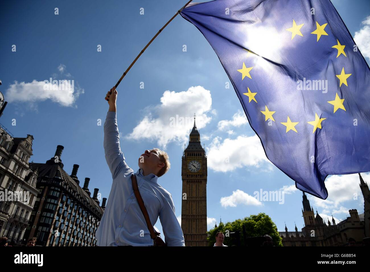Protester waves a European Union flag outside the houses of Parliament, Westminster on the day of the EU Referendum - Stock Image