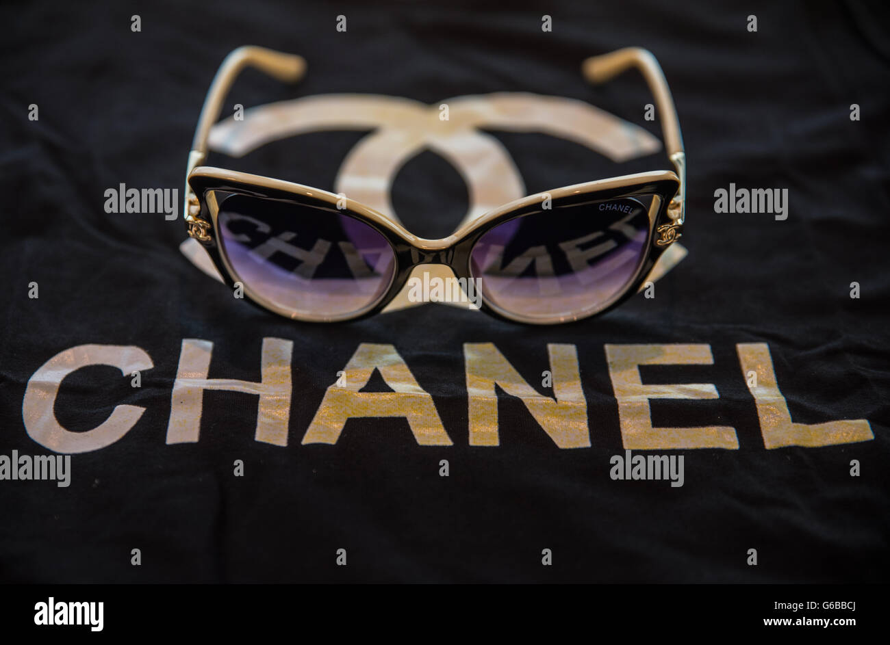 bdecc94fd3b A pair of counterfeit Chanel sunglasses seen on top of a knockoff t-shirt of