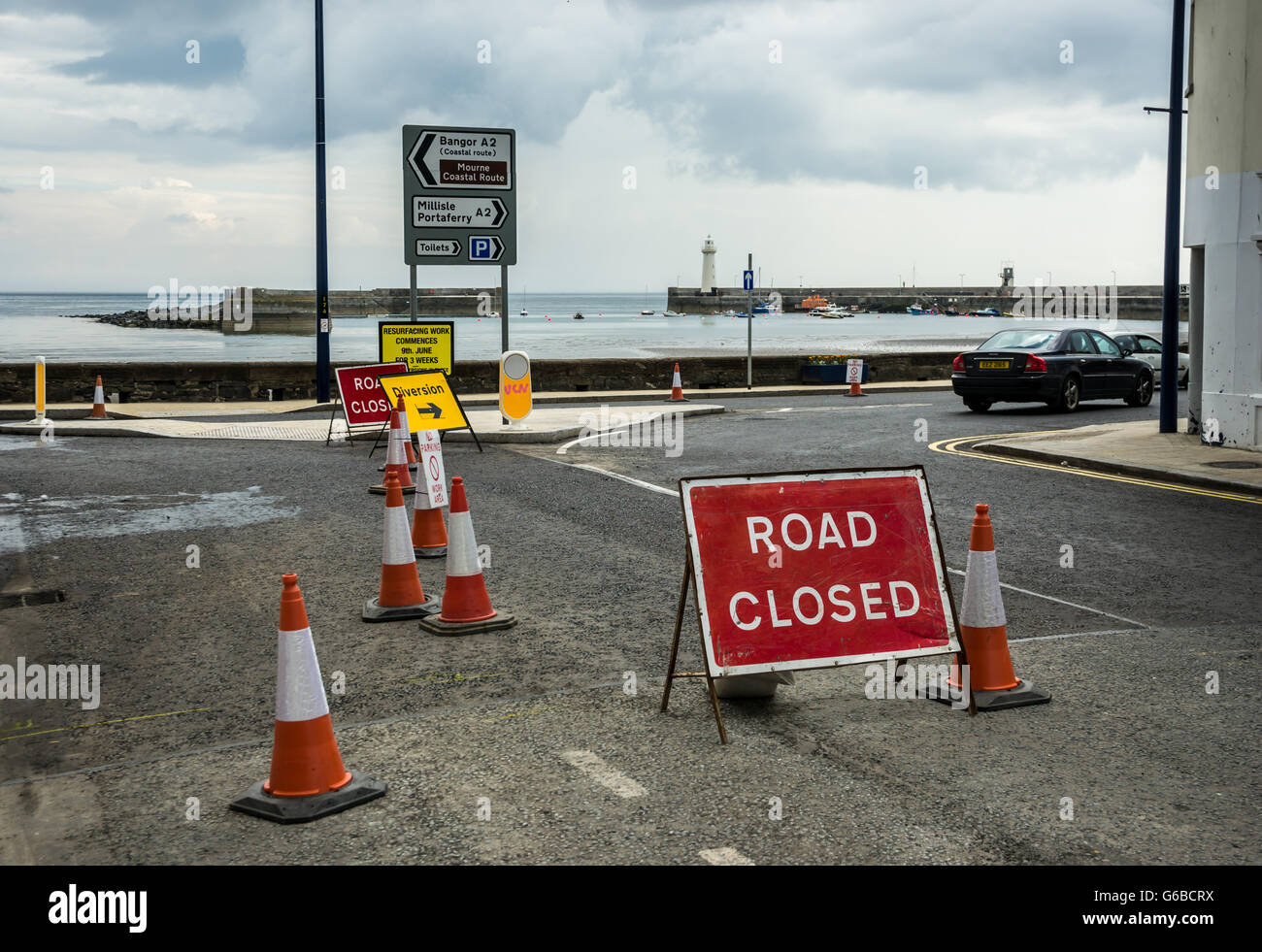 Donaghadee, County Down, UK  24th June 2016  Roadworks and signage  Roadsigns with Donaghadee lighthouse and harbour - Stock Image