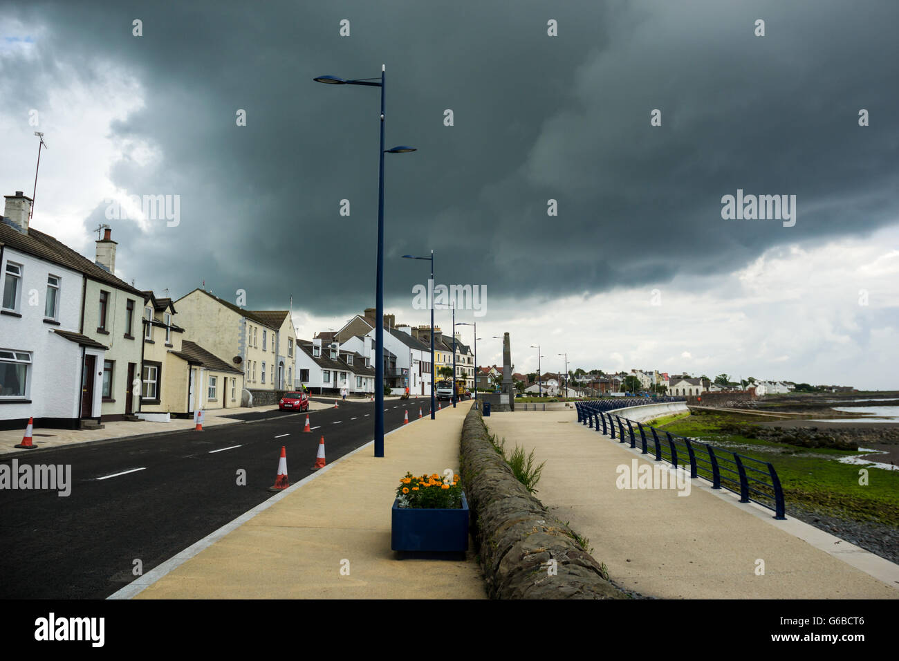 Donaghadee, County Down, UK  24th June 2016  Roadworks   Traffic cones preventing parking with dark brooding sky - Stock Image