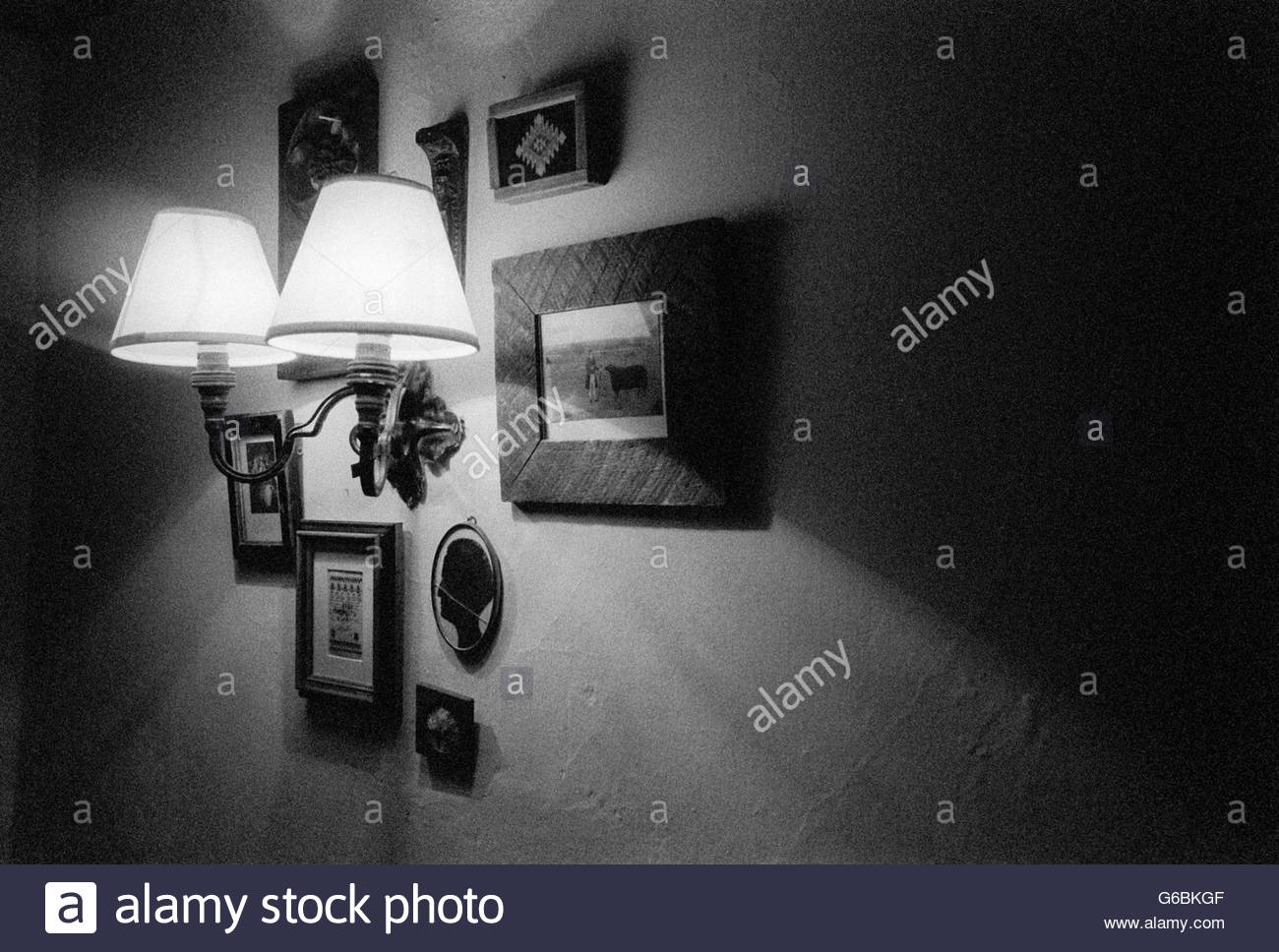 Pictures on a wall in a cottage, centred around lights - Stock Image