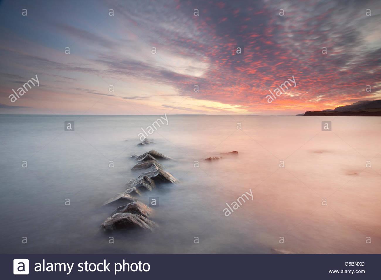Rocks protruding through a gentle sea. - Stock Image