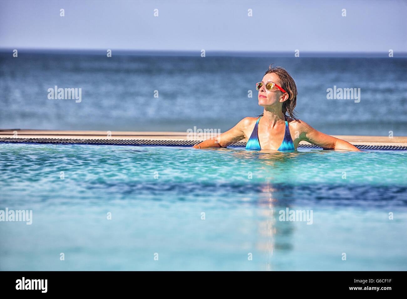 Woman sunbathing by a pool in Nilaveli. Sri Lanka - Stock Image