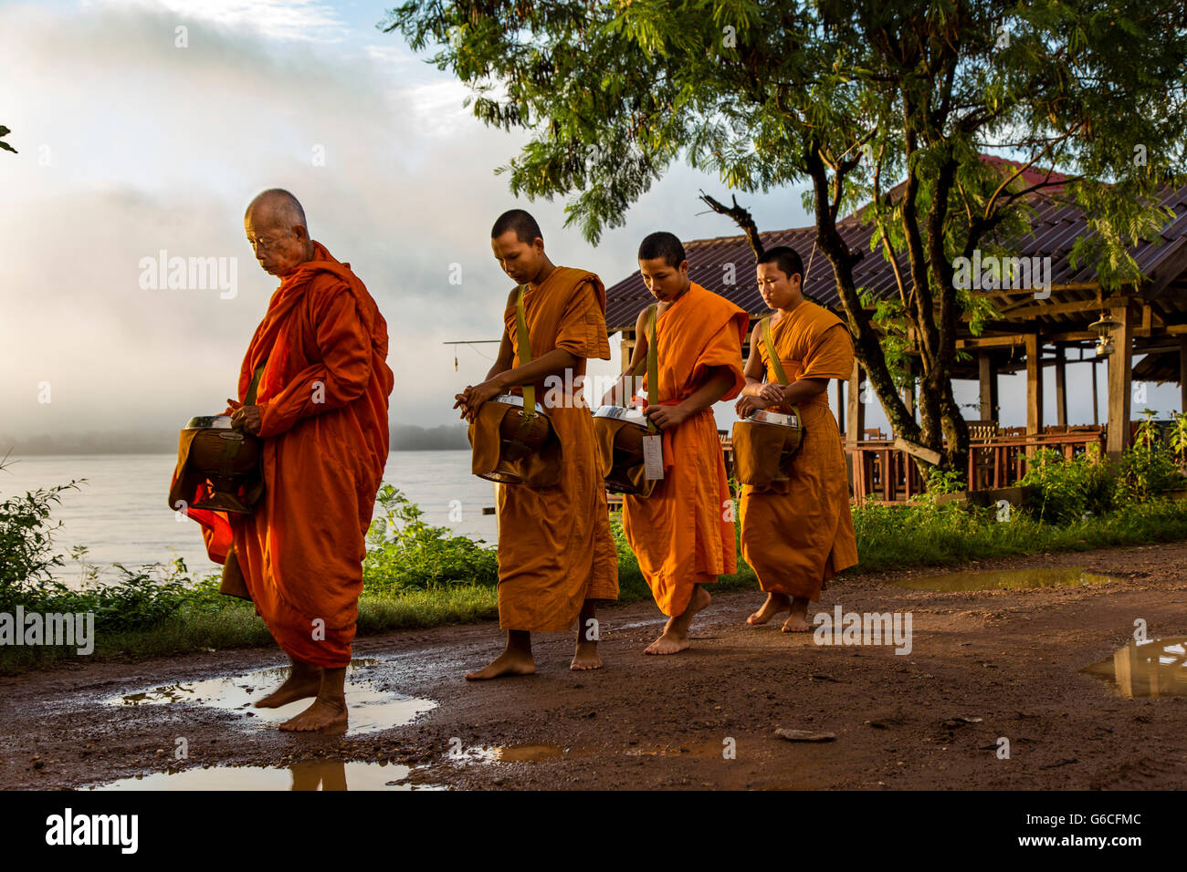 Buddhist Monks during Morning Alms Giving on Don Khong Island in Southern Laos Stock Photo