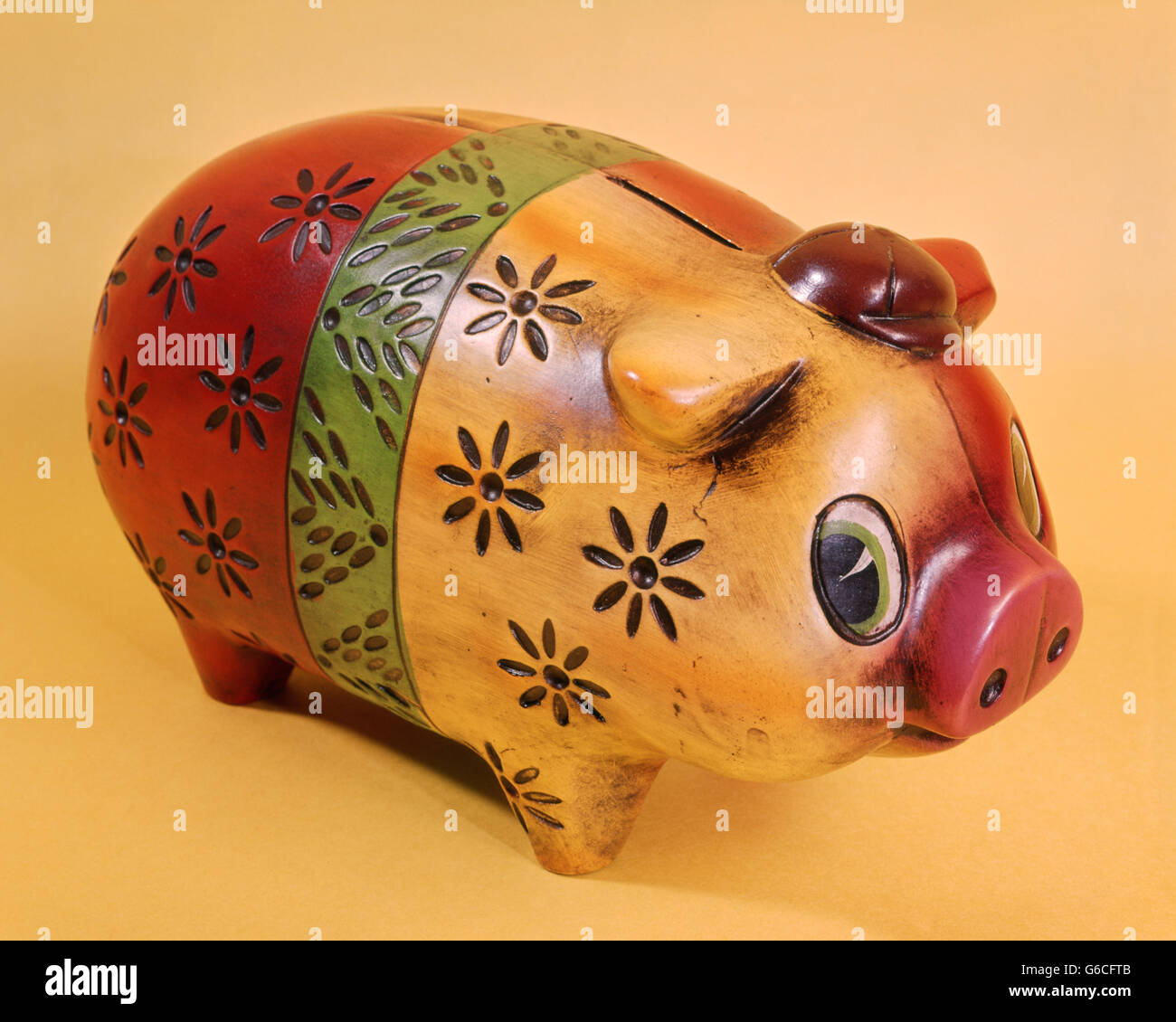 1970s PAINTED AND CARVED WOODEN PIGGY BANK RED GREEN YELLOW BANDS - Stock Image