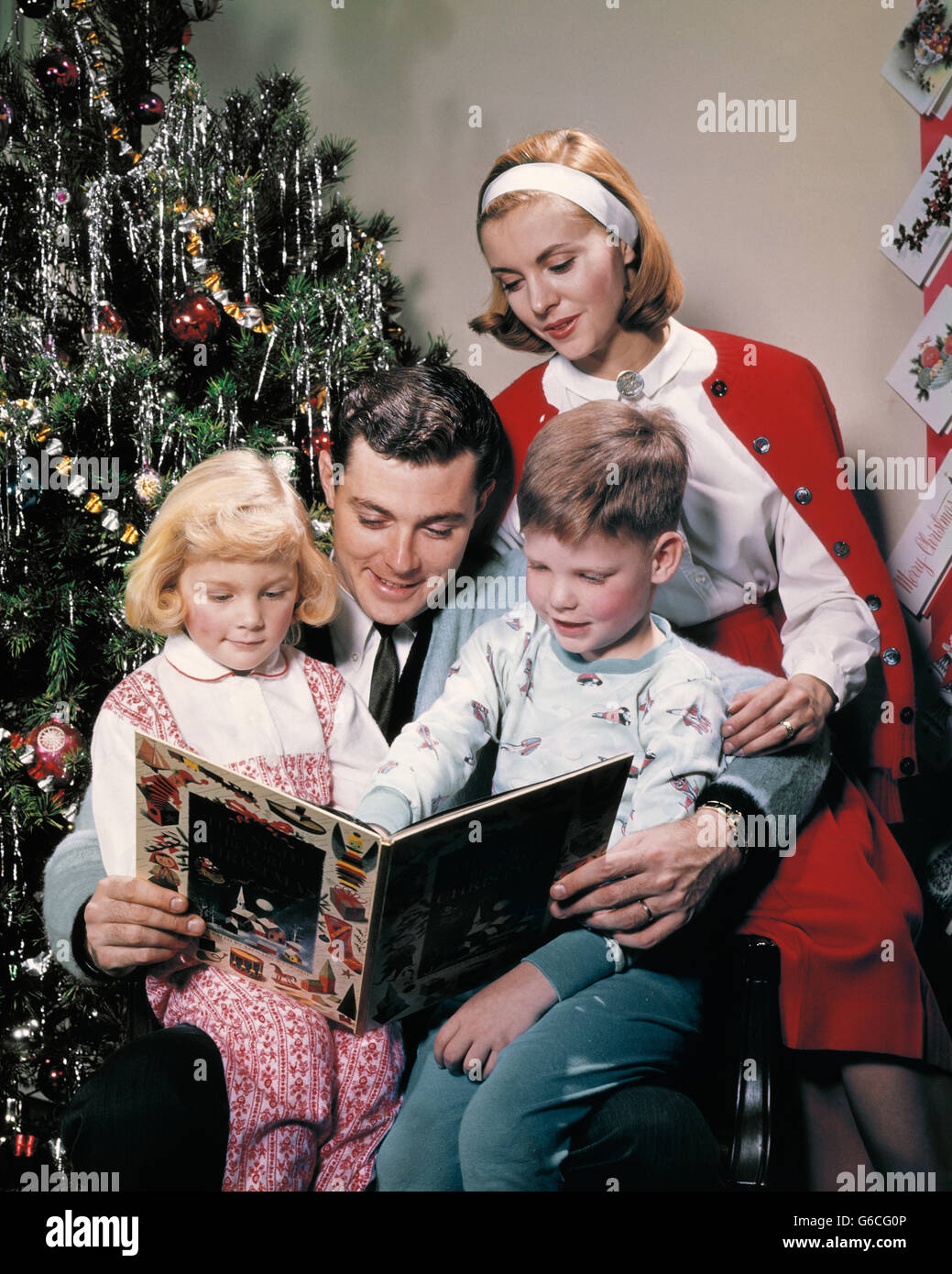 1960s FAMILY BY CHRISTMAS TREE FATHER READING BOOK THE NIGHT BEFORE CHRISTMAS TO SON DAUGHTER WIFE - Stock Image