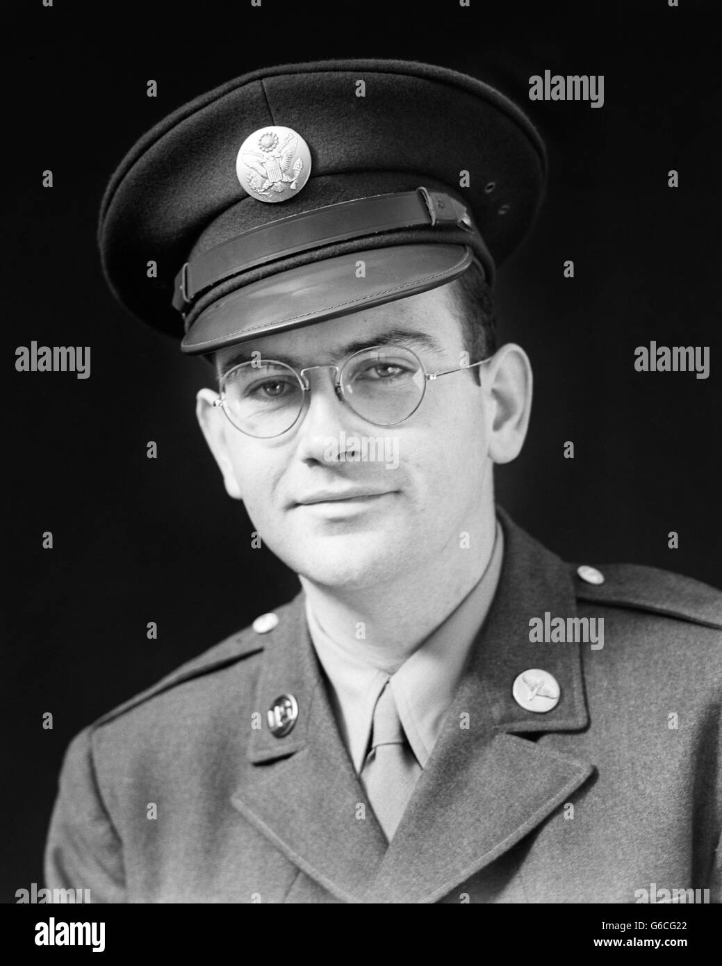1940s PORTRAIT OF MAN WORLD WAR II ENLISTED SOLDIER WEARING ARMY UNIFORM LOOKING AT CAMERA - Stock Image