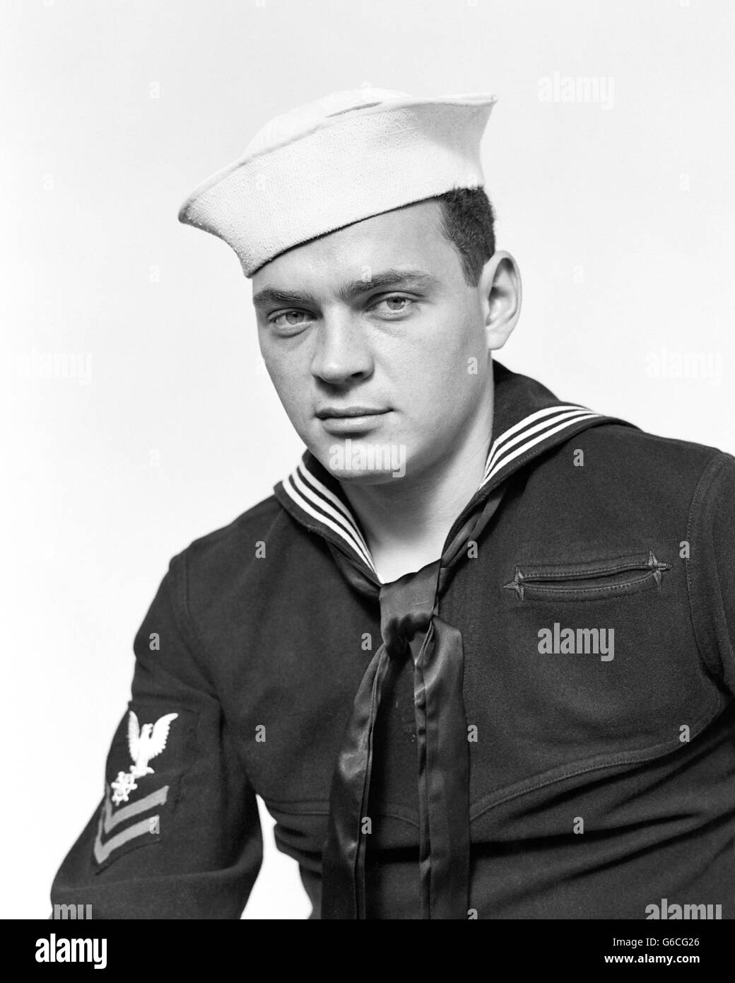 1940s PORTRAIT SERIOUS AMERICAN SAILOR WEARING NAVY UNIFORM LOOKING AT CAMERA Stock Photo