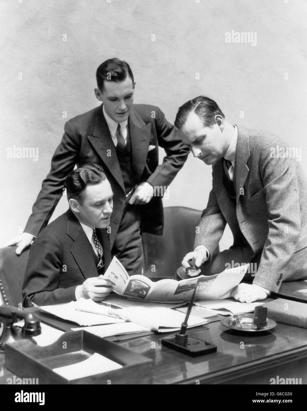 1930s THREE MEN AT DESK IN OFFICE LOOKING AT BROCHURE - Stock Image