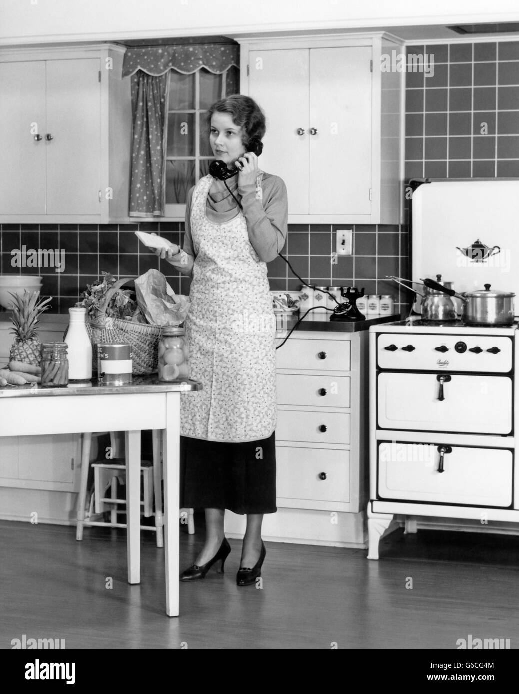 1930s WOMAN IN KITCHEN GROCERIES ON TABLE TALKING ON TELEPHONE - Stock Image