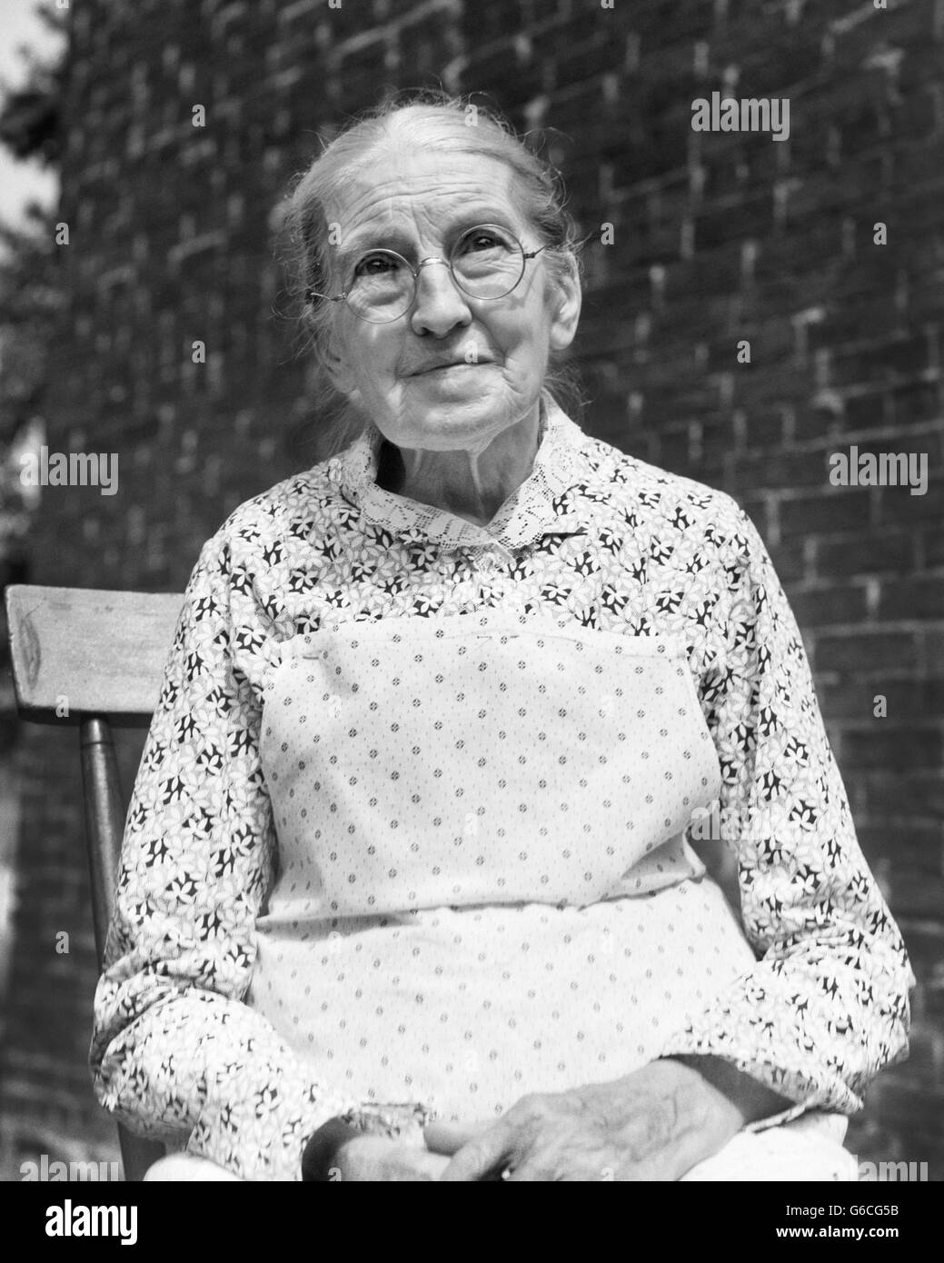 1930s PORTRAIT ELDERLY WOMAN WEARING EYEGLASSES PRINT DRESS WHITE BIB APRON - Stock Image