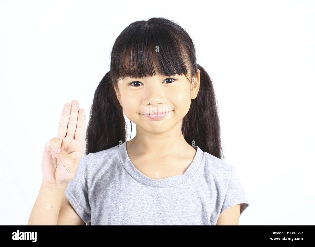 Portrait of young cute girl posting with three fingers isolated on white - Stock Image