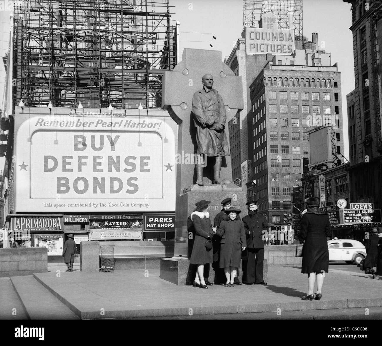1940s SAILORS & WOMEN POSE AT FATHER DUFFY STATUE BUY DEFENSE BONDS BILLBOARD WARTIME WW2 1942 TIMES SQUARE - Stock Image