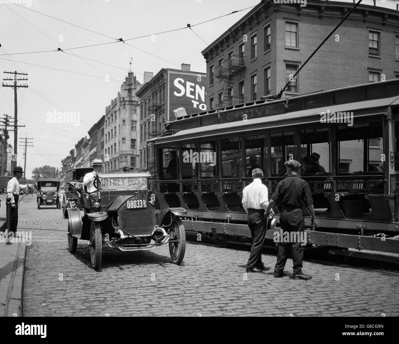 1910s JITNEY BUS AND OPEN ELECTRIC TROLLEY CAR ON BRICK STREET IN HOBOKEN NEW JERSEY USA - Stock Image