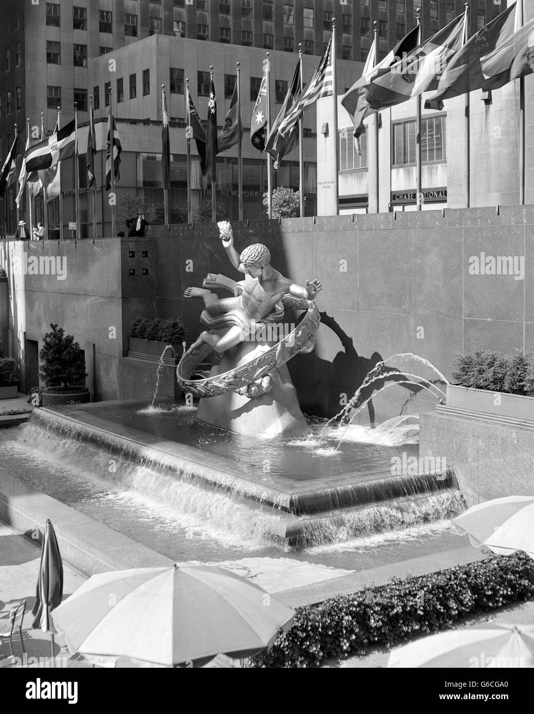 1950s ROCKEFELLER CENTER PROMETHEUS FOUNTAIN BY PAUL MANSHIP AND UNITED NATIONS FLAGS NEW YORK CITY NY USA - Stock Image