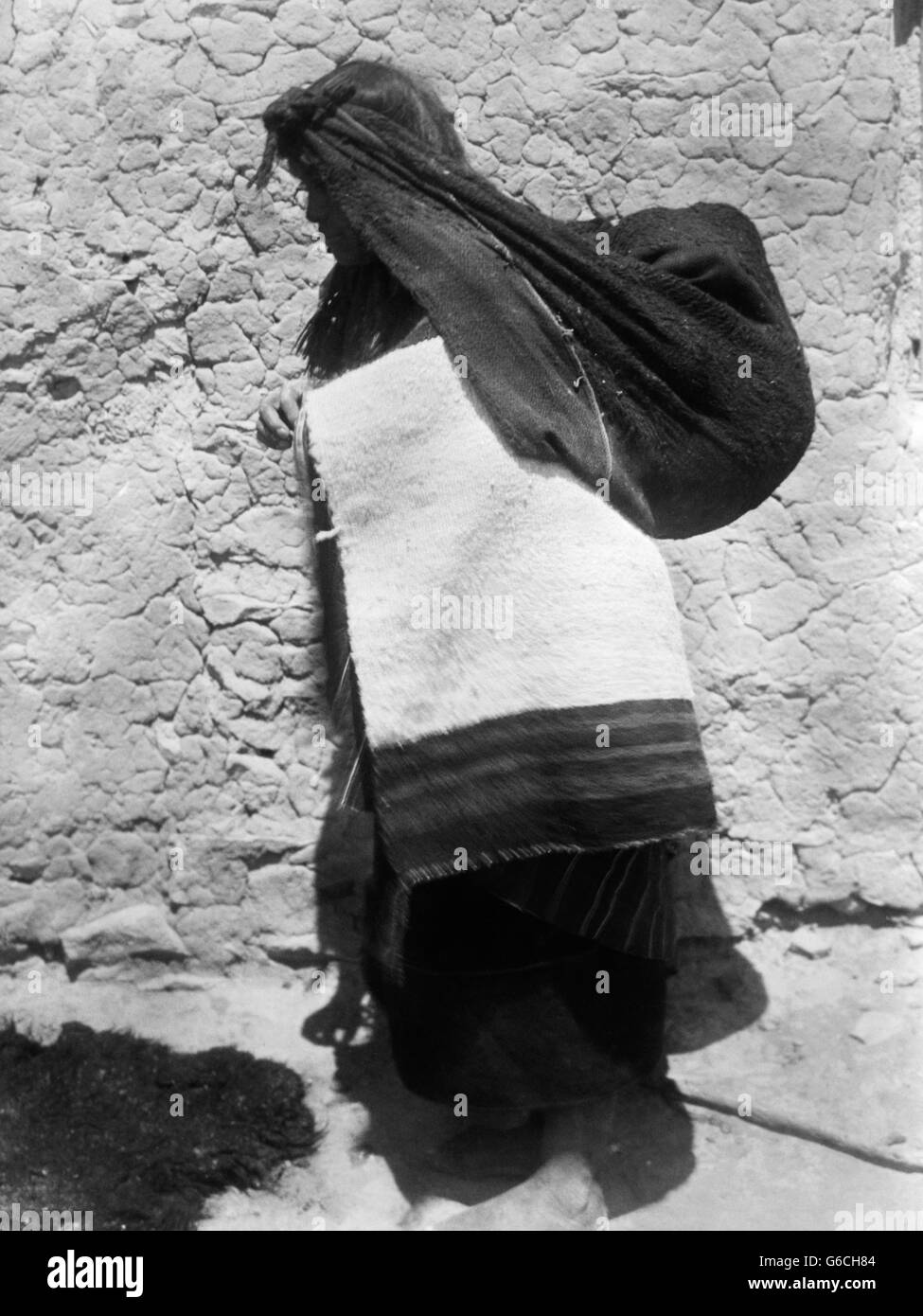 1890s NATIVE AMERICAN INDIAN WOMAN WEARING BLANKET USING A TUMPLINE TO CARRY A BUNDLE ON HER BACK - Stock Image