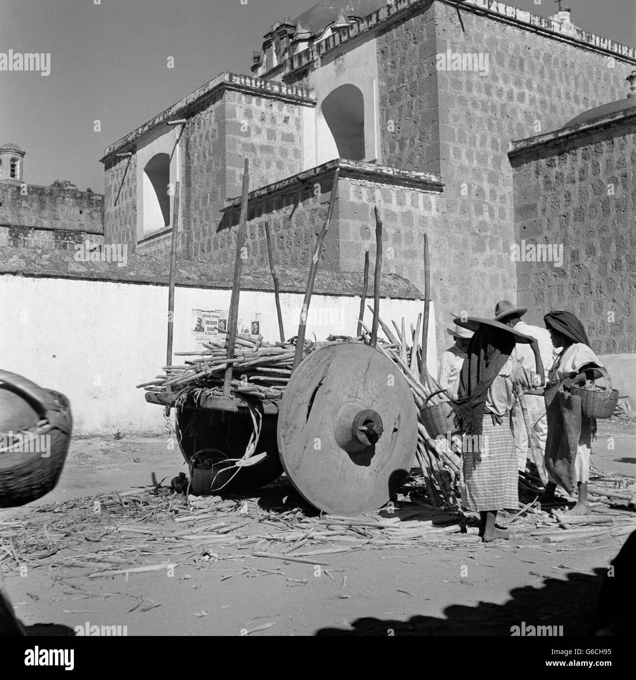 1930s OX CART LOADED WITH SUGAR CANE AND VENDORS IN OUTDOOR MARKET OAXACA MEXICO - Stock Image