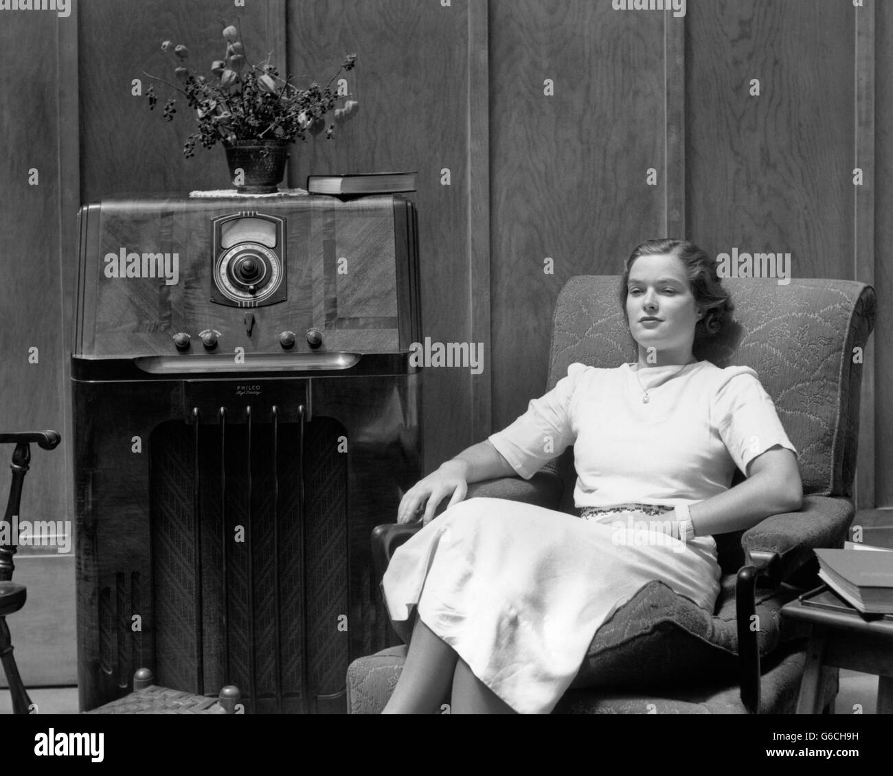 1930s 1940s SERIOUS WOMAN SITTING IN LIVING ROOM LISTENING TO RADIO - Stock Image