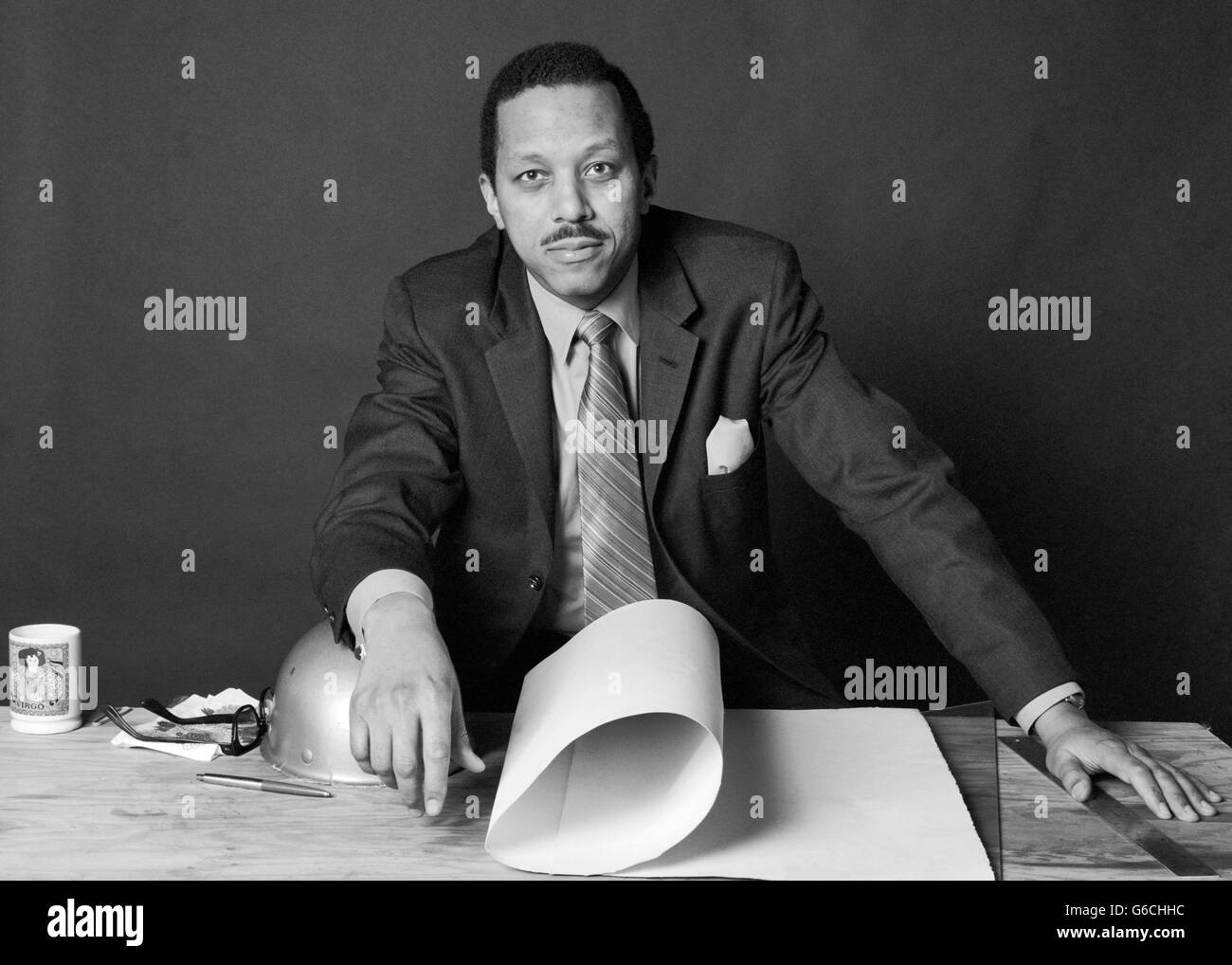 1970s AFRICAN-AMERICAN BUSINESSMAN CONTRACTOR ARCHITECT BUILDER AT TABLE WITH BUILDING PLANS AND HARD HAT LOOKING - Stock Image
