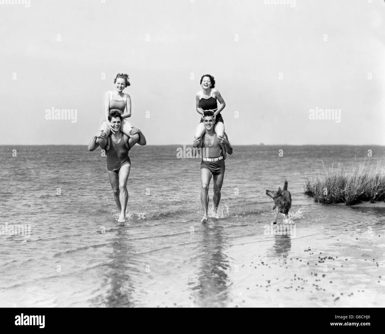 1930s TWO COUPLES RUNNING IN OCEAN WEARING BATHING SUITS GIRLS SITTING ON BOYS SHOULDERS AND DOG RUNNING ALONG SIDE Stock Photo