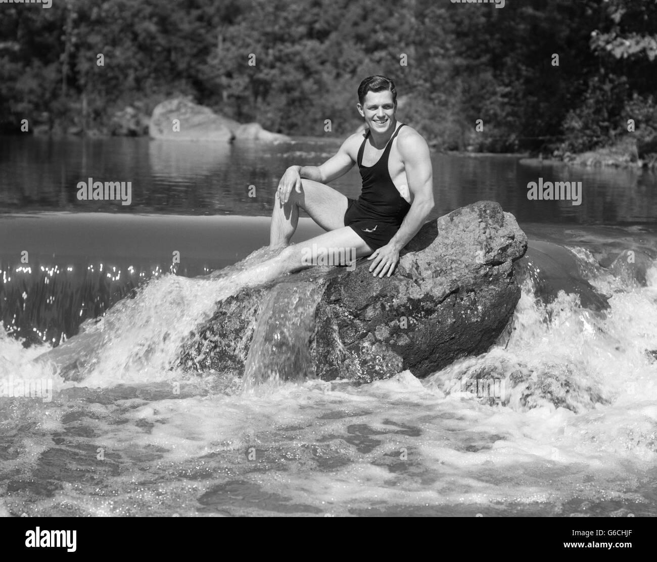 1930s SMILING MAN LOOKING AT CAMERA WEARING BATHING SUIT TANK TOP SWIM TRUNKS POSING SITTING ON LARGE ROCK IN WOODLAND - Stock Image