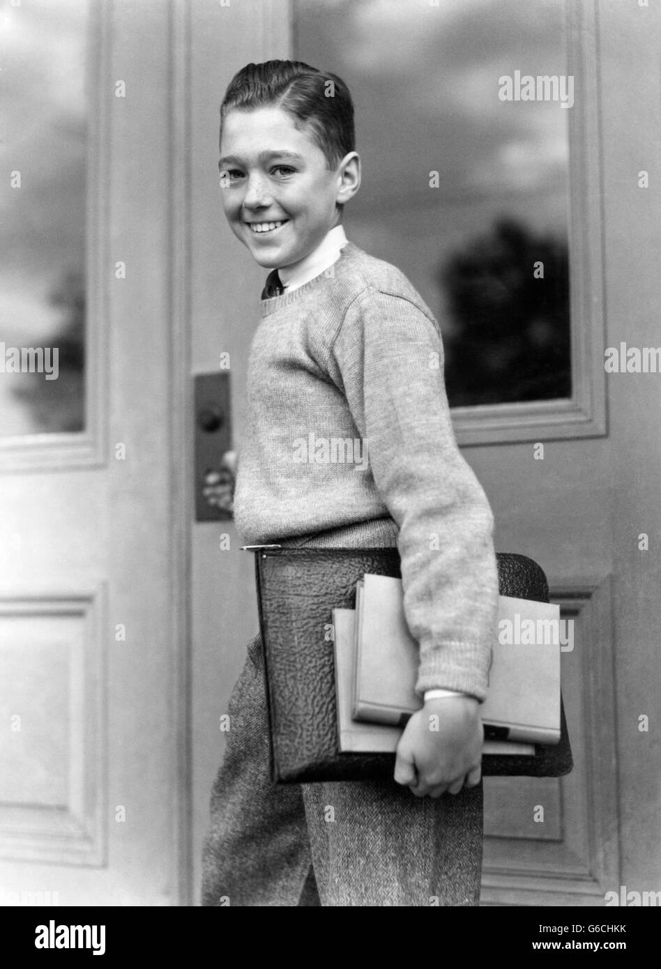 1930s SMILING BOY STUDENT CARRYING TEXTBOOKS STANDING BY SCHOOL DOOR ENTRANCE LOOKING AT CAMERA - Stock Image