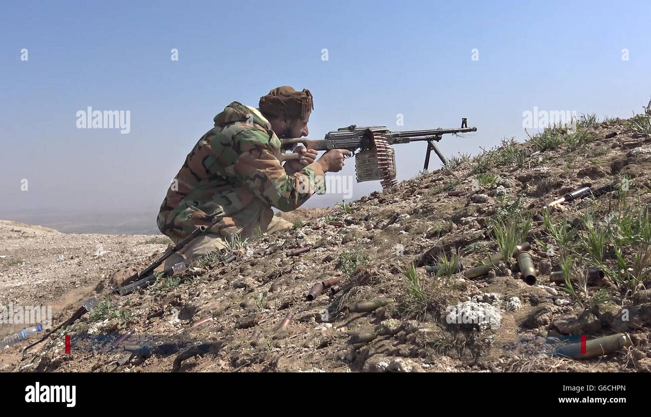 Islamic State fighter fires PK machine gun during fighting in the Makhoul Mountains May 30, 2016 near Baiji, Iraq. - Stock Image
