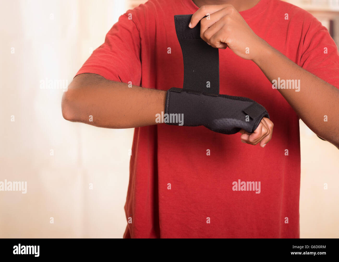 Closeup man in red shirt wearing black wrist brace support on right hand, tightening velcro using other arm - Stock Image