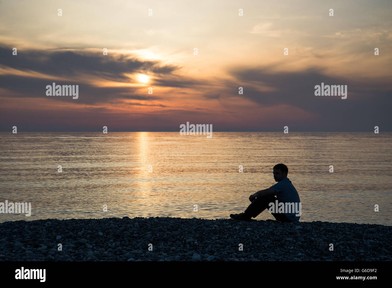Sad man silhouette worried on the beach at sunset with the sun in the background - Stock Image